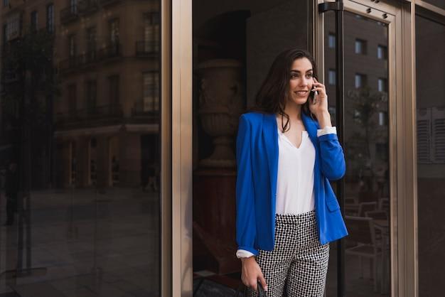 Lächelnde geschäftsfrau mit handy neben einer glastür Kostenlose Fotos