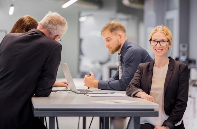 Lächelnde geschäftsfrau vor ihrem kollegen, der am arbeitsplatz arbeitet Kostenlose Fotos