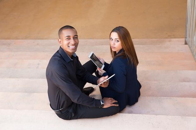 Lächelnde geschäftsleute, die tabletten halten und auf treppe sitzen Kostenlose Fotos