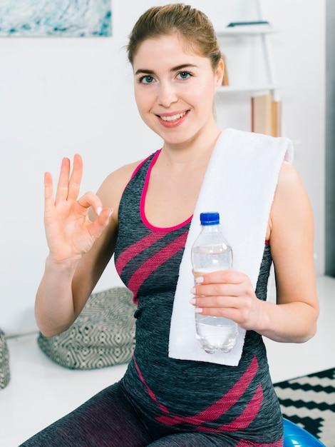 Lächelnde gesunde junge frau, die in der hand wasserflasche zeigt okayzeichen hält Kostenlose Fotos