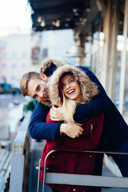 Lächelnde glückliche europäische paare der junge, die im winter umarmen Kostenlose Fotos