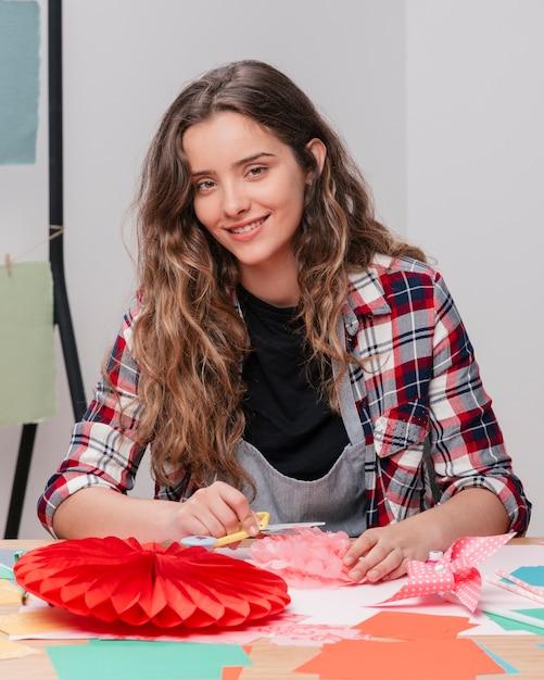 Lächelnde handwerkerin, die kamera beim arbeiten betrachtet Kostenlose Fotos