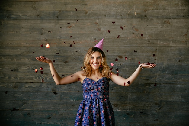 Lächelnde herrliche frau, die einen feiertag, spielend mit konfettis feiert Kostenlose Fotos
