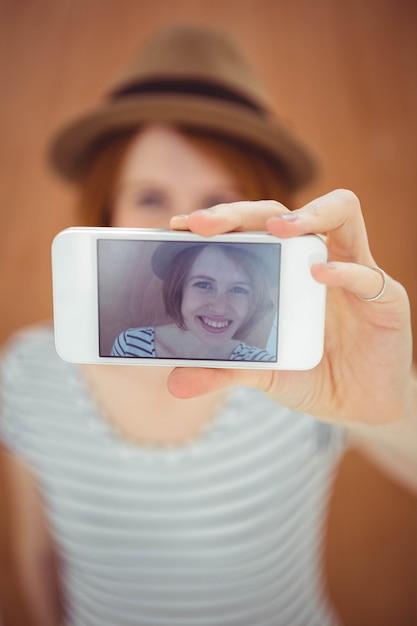 Lächelnde hippie-frau, die ein selfie nimmt Premium Fotos
