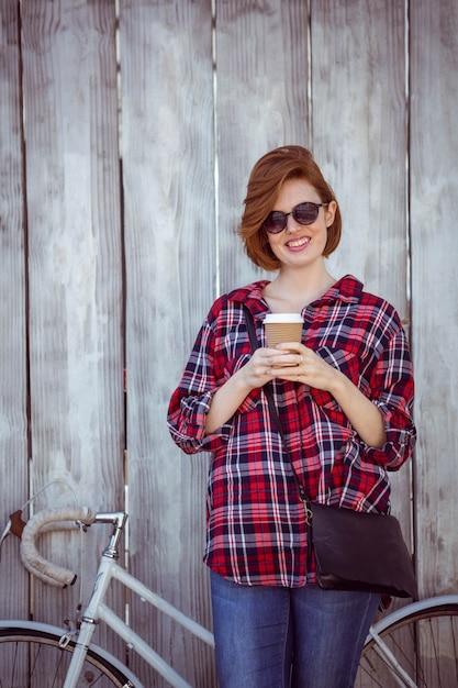 Lächelnde hippie-frau mit dem kaffee und einem fahrrad, stehend Premium Fotos