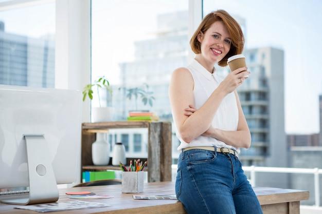 Lächelnde hippie-geschäftsfrau, lehnend auf ihrem schreibtisch und trinken kaffee Premium Fotos