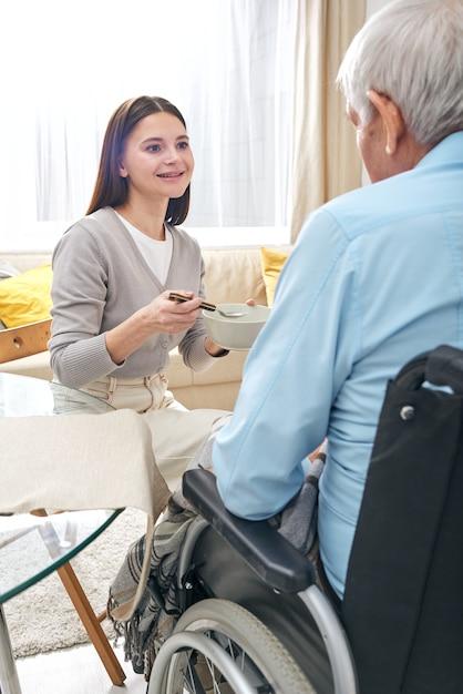 Lächelnde hübsche krankenschwester, die älteren behinderten mann im rollstuhl füttert und mit ihm im wohnzimmer spricht Premium Fotos