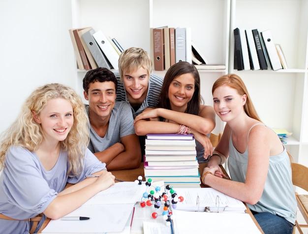 Lächelnde jugendliche, die wissenschaft in einer bibliothek studieren Premium Fotos