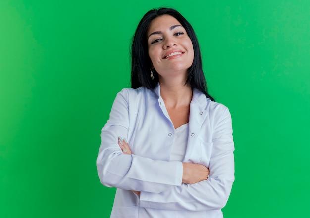 Lächelnde junge ärztin, die medizinische robe trägt und mit geschlossener haltung steht Kostenlose Fotos