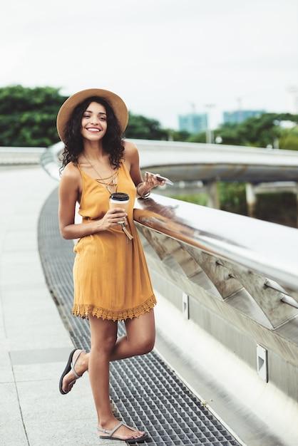 Lächelnde junge beiläufig gekleidete frau, die auf flussufer aufwirft Kostenlose Fotos