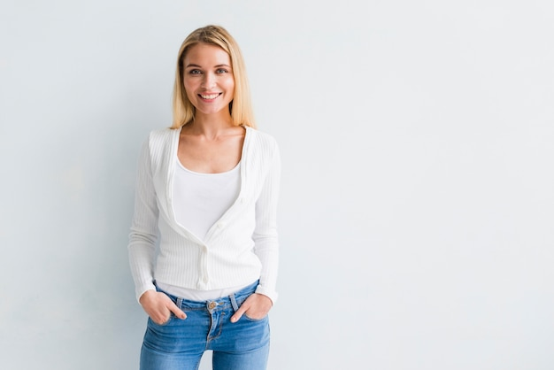 Lächelnde junge blonde frau in der beiläufigen kleidung Kostenlose Fotos