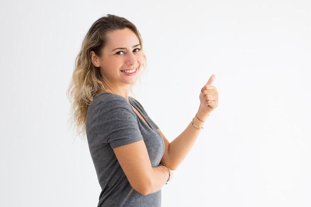 Lächelnde junge dame, die sich daumen zeigt und kamera betrachtet Kostenlose Fotos