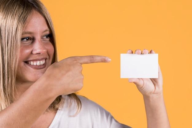 Lächelnde junge frau der unfähigkeit, die über unbelegte visitenkarte zeigt Kostenlose Fotos