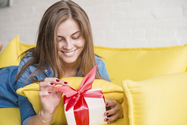 Lächelnde junge frau, die an vom sofa auspackt ihr geburtstagsgeschenk liegt Kostenlose Fotos