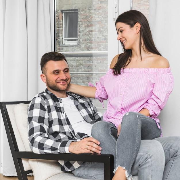 Lächelnde junge frau, die auf dem schoss ihres freundes sitzt auf stuhl sitzt Kostenlose Fotos