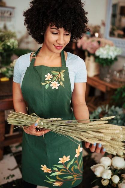 Lächelnde junge frau, die auf dem shop hält bündel ährchen steht Kostenlose Fotos
