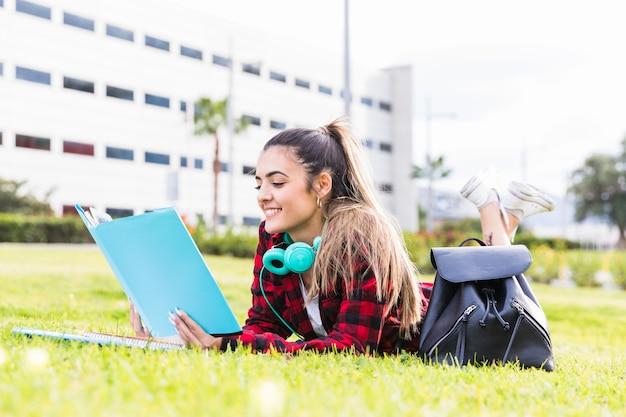 Lächelnde junge frau, die auf den rasen liest das buch am universitätsgelände legt Kostenlose Fotos