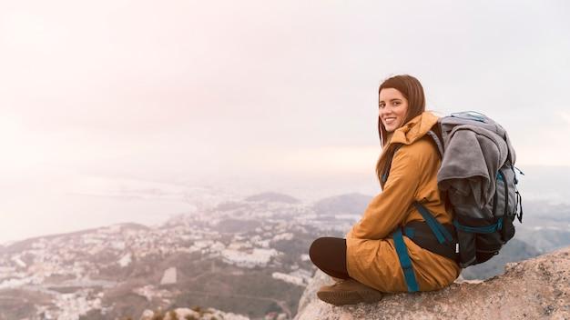 Lächelnde junge frau, die auf die oberseite des berges mit ihrem rucksack sitzt Kostenlose Fotos