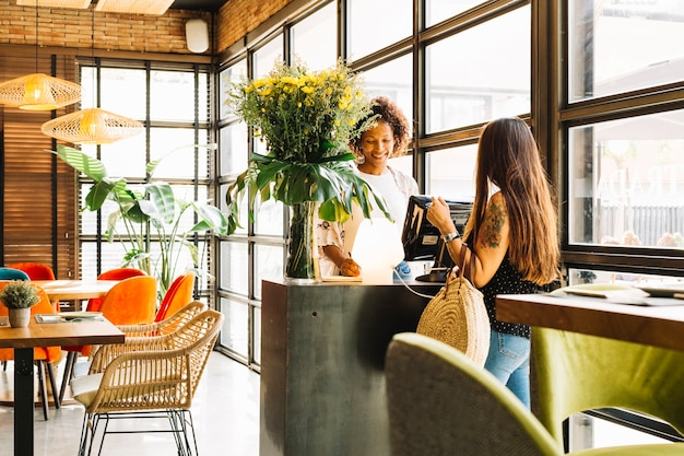 Lächelnde junge frau, die bestellung vom weiblichen kunden im restaurant entgegennimmt Kostenlose Fotos
