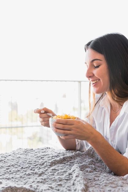 Lächelnde junge frau, die das corn-flakes-frühstück genießt Kostenlose Fotos