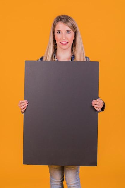 Lächelnde junge frau, die das leere schwarze plakat in der hand betrachtet kamera gegen orange hintergrund hält Kostenlose Fotos