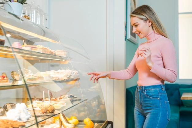 Lächelnde junge frau, die den kuchen steht vor glasschrank wählt Kostenlose Fotos