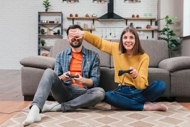 Lächelnde junge frau, die den steuerknüppel bedeckt die augen ihres ehemanns beim spielen des videospiels hält Kostenlose Fotos