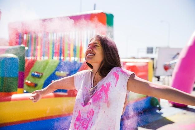 Lächelnde junge frau, die die holi farbe genießt Kostenlose Fotos