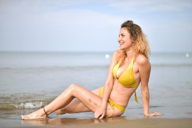 Lächelnde junge frau, die einen badeanzug am strand trägt - das konzept des glücks Kostenlose Fotos
