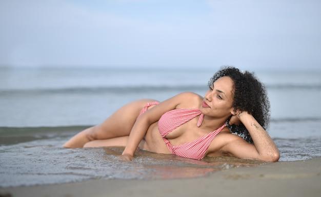 Lächelnde junge frau, die einen badeanzug im strand trägt Kostenlose Fotos