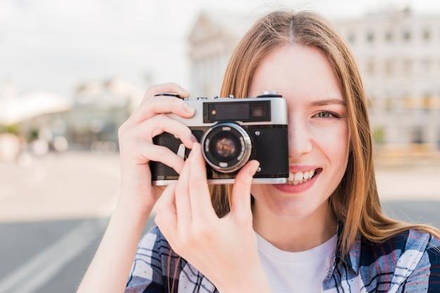 Lächelnde junge frau, die foto mit kamera an draußen macht Kostenlose Fotos