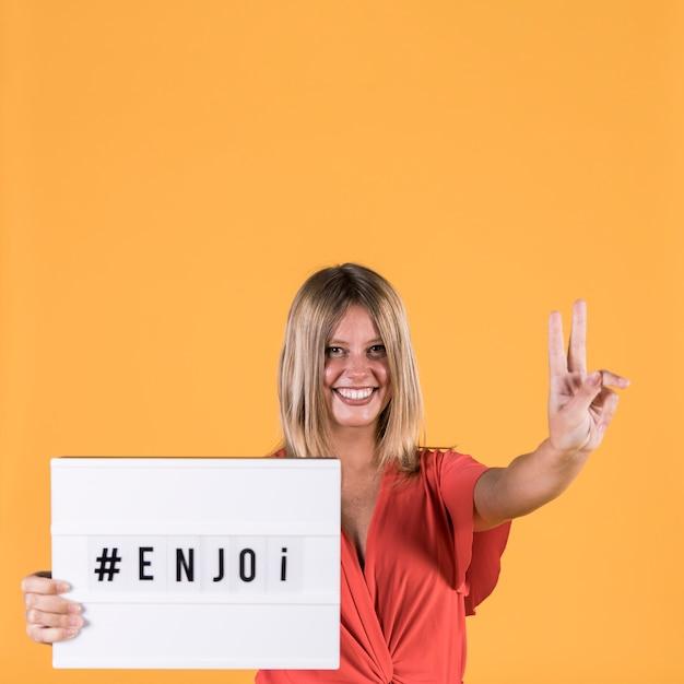 Lächelnde junge frau, die friedenszeichen beim halten des leuchtkasten mit text zeigt Kostenlose Fotos