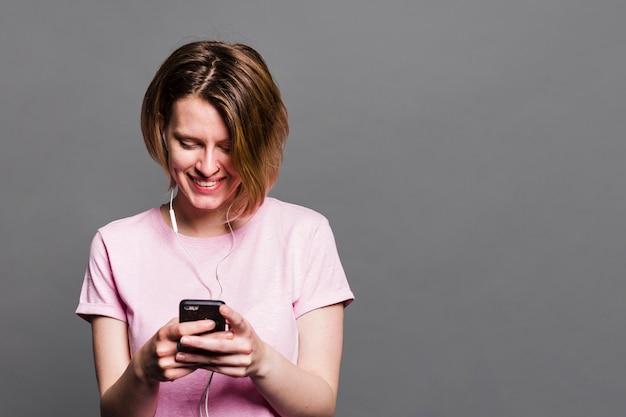 Lächelnde junge frau, die handy gegen graue wand verwendet Kostenlose Fotos