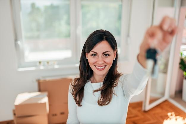 Lächelnde junge frau, die hausschlüssel ihres neuen hauses hält. immobilien- und umzugskonzept. Premium Fotos
