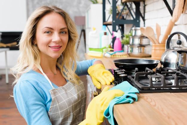 Lächelnde junge frau, die hölzerne küchenarbeitsplatte abwischt Kostenlose Fotos