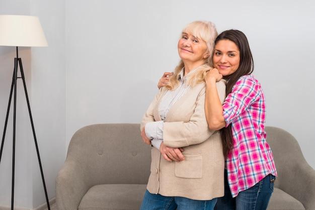 Lächelnde junge frau, die ihre ältere mutter von hinten steht vor sofa umfasst Kostenlose Fotos