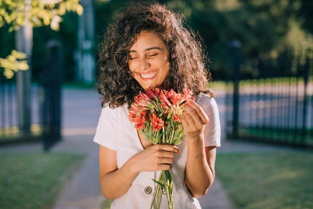 Lächelnde junge frau, die in der hand blumenblumenstrauß hält Kostenlose Fotos