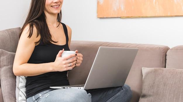 Lächelnde junge frau, die in der hand kaffeetasse unter verwendung des laptops hält Kostenlose Fotos