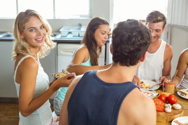 Lächelnde junge frau, die mit freunden zu hause frühstückt Premium Fotos