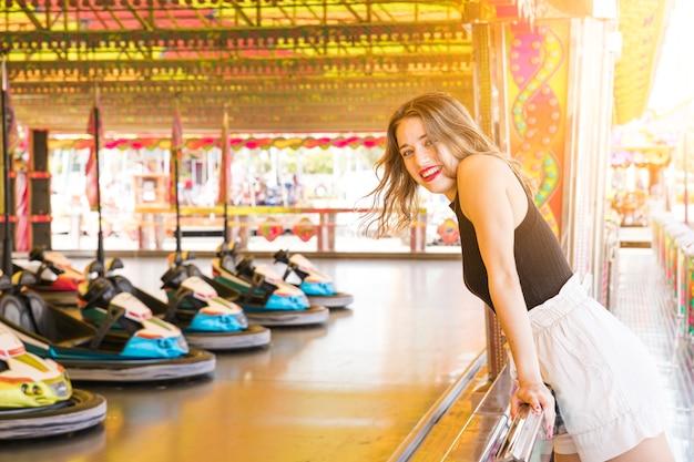 Lächelnde junge frau, die nahe der autoautofahrt genießt Kostenlose Fotos