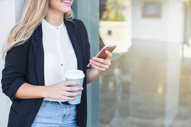 Lächelnde junge frau, die papierkaffeetasse und handy hält Kostenlose Fotos