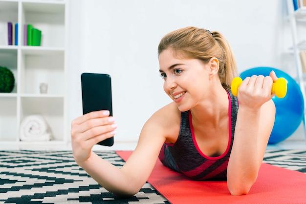 Lächelnde junge frau, die selfie am handy beim handeln von übung mit gelbem dummkopf nimmt Kostenlose Fotos