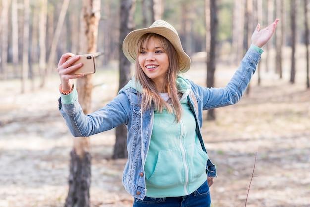 Lächelnde junge frau, die selfie am handy im wald nimmt Kostenlose Fotos