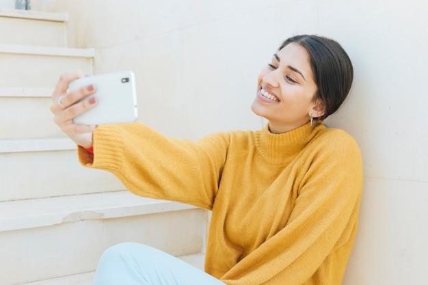 Lächelnde junge frau, die selfie am handy nimmt Kostenlose Fotos