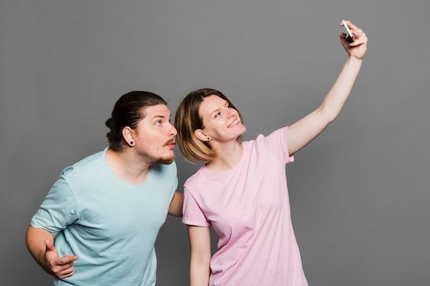 Lächelnde junge frau, die selfie mit ihrem freund gegen grauen hintergrund nimmt Kostenlose Fotos