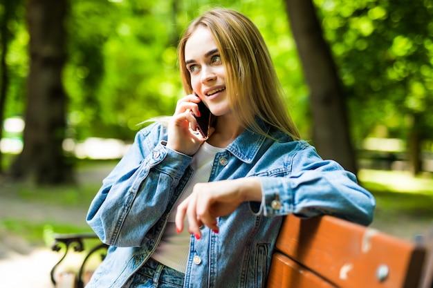 Lächelnde junge frau, die smartphone auf stadtstraße anruft Kostenlose Fotos