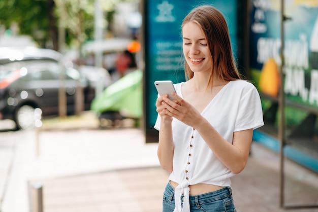 Lächelnde junge frau, die smartphone hält und den schirm steht im freien betrachtet Premium Fotos