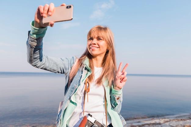 Lächelnde junge frau, die vor dem meer nimmt selfie auf smartphone steht Kostenlose Fotos