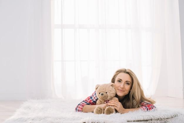 Lächelnde junge frau, die zu hause auf pelz mit teddybären liegt Kostenlose Fotos