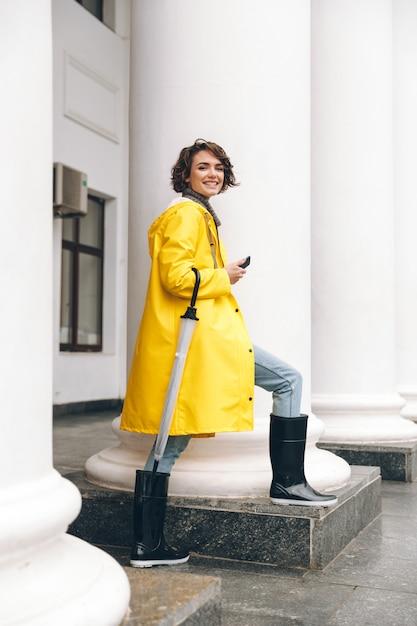 Lächelnde junge frau im regenmantel gekleidet Kostenlose Fotos